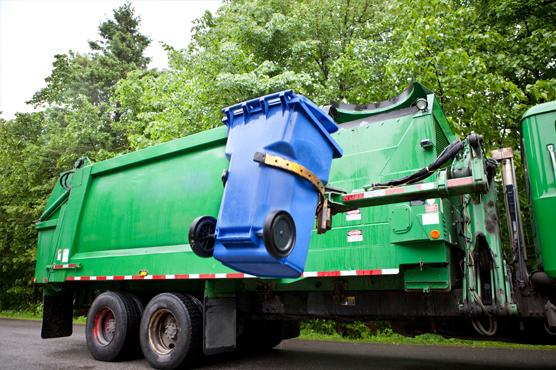Garbage truck picking up garbage can